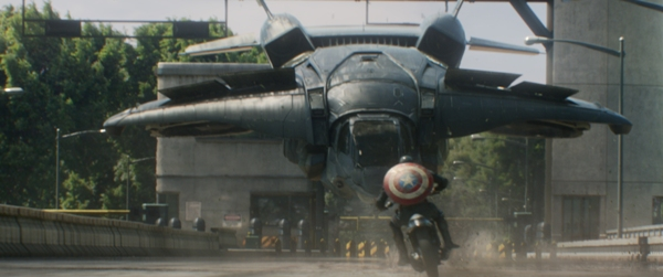Captain America playing chicken on a motorcycle with a jet