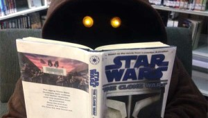 Jawa reading Star Wars The Clone Wars book in the library