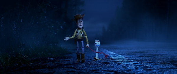Woody and Forky walk along a dark road in Toy Story 4